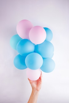 Female hand holding a set small pink and blue baloons lika a cloud on white background