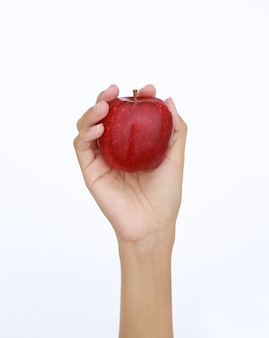 Female hand holding and showing a red apple on white background
