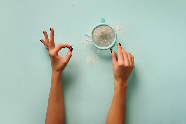 Female hand holding sieve flour on blue background.