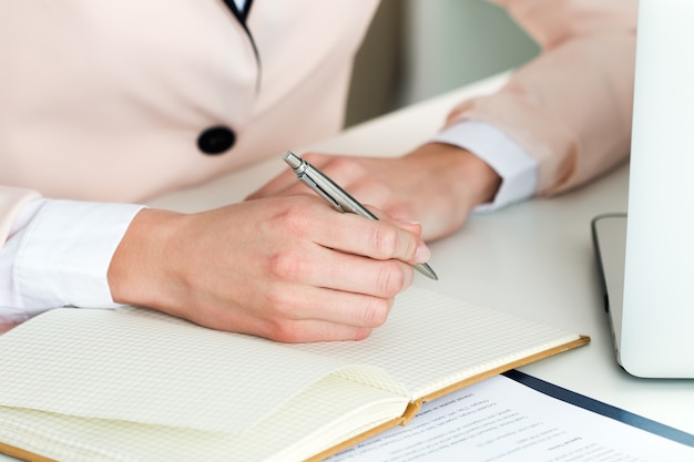 銀のペンのクローズアップを持っている女性の手