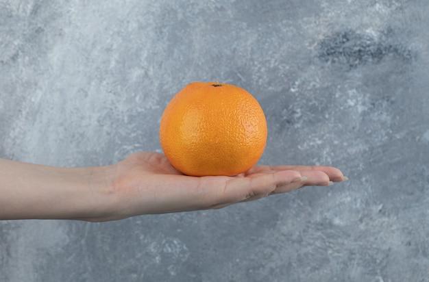 Mano femminile che tiene singola arancia sul tavolo di marmo.