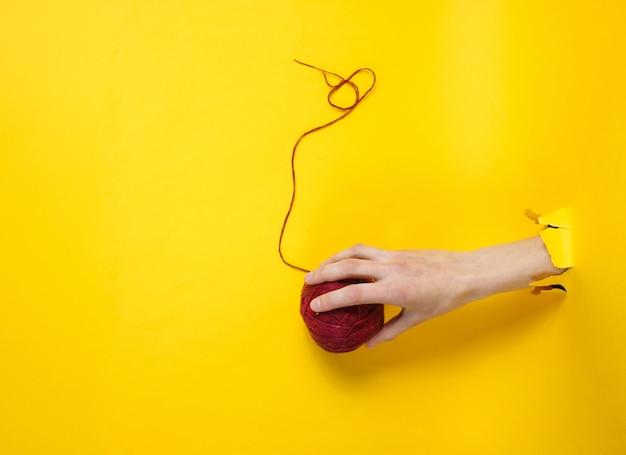 引き裂かれた黄色い紙を通して糸のかせを持っている女性の手。ミニマルな創造的な医学の概念