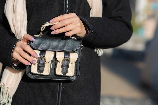 小さな革製の財布を持っている女性の手。空きスペース