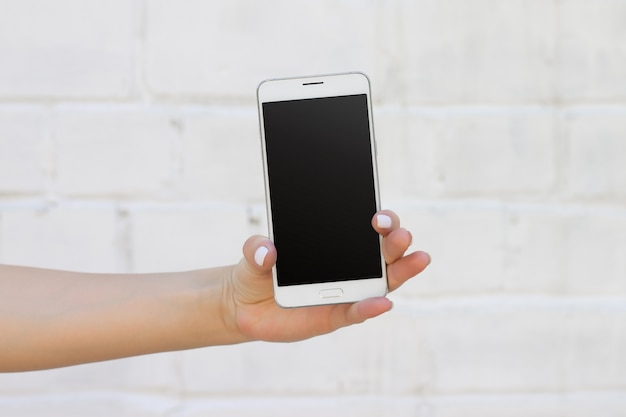 Female hand holding smartphone on white brick wall background