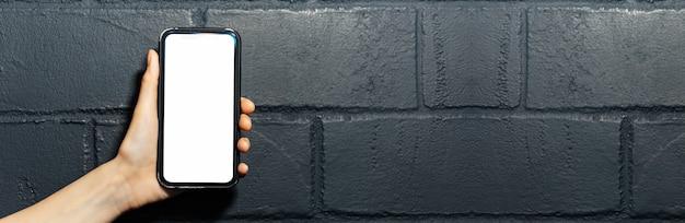 黒レンガの壁の背景にモックアップとスマートフォンを持っている女性の手。