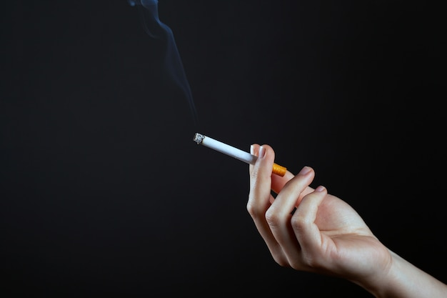 Female hand holding a smoking cigarettecopy space. harm from smoking cigarettes.