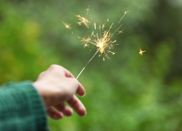 ぼやけた表面に線香花火を持っている女性の手