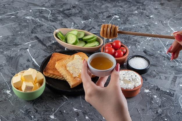 Женская рука, держащая ложку меда на столе для завтрака.