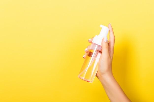 Female hand holding spray cream bottle of lotion.