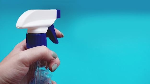 Женская рука держит спрей с моющим средством на синем фоне. работа по дому, ведение домашнего хозяйства и концепция домашнего хозяйства