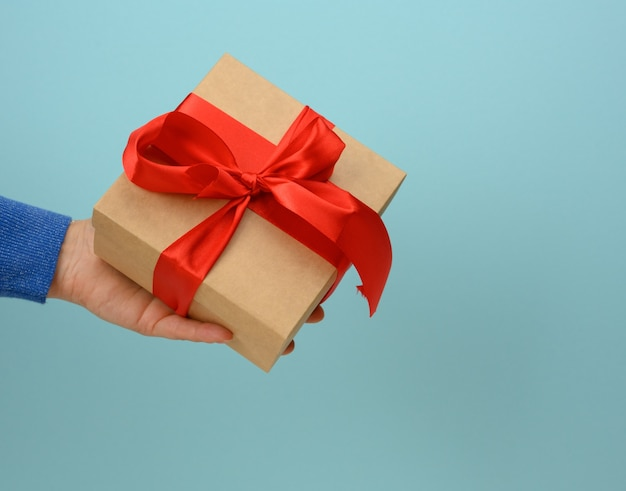 Female hand holding a square box tied with a red ribbon on a blue surface, surprise