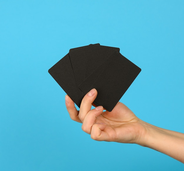 Female hand holding a stack of blank black business cards, blue background