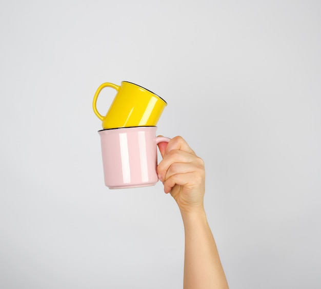 Female hand holding a stack of ceramic mugs