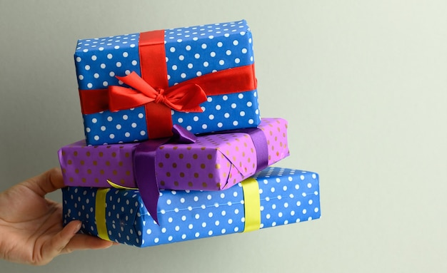 Female hand holding a stack of gift boxes tied with silk ribbon on a gray background, surprise and win