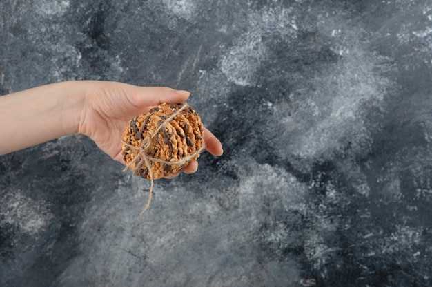 Female hand holding stack of oatmeal cookies on marble background.