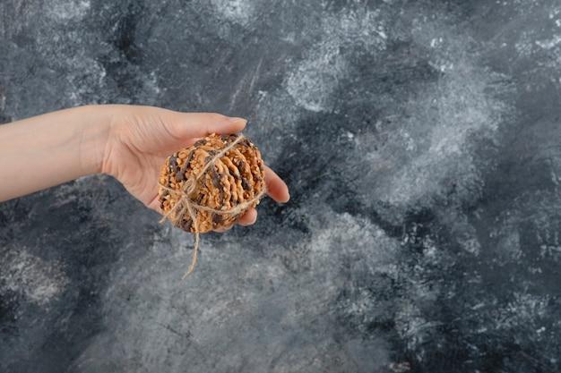 Женская рука, держащая стек овсяного печенья на мраморном фоне.