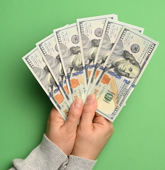 Female hand holding a stack of paper one hundred dollar bills on a green background