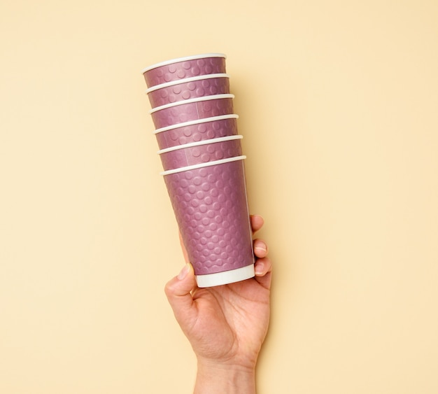 Female hand holding stack of purple disposable paper cups on beige background, zero waste