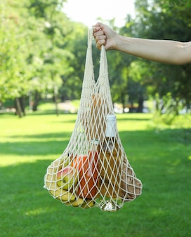 Женская рука держит мешок строки в парке