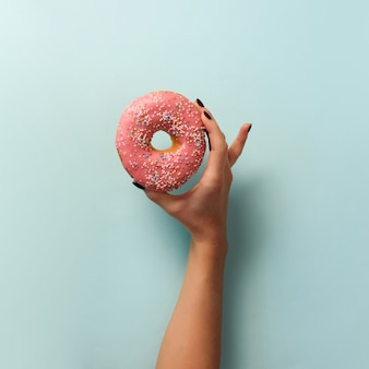 Female hand holding sweet donut over blue background. top view, flat lay.