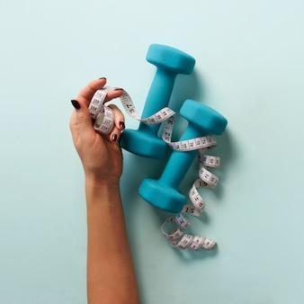 Female hand holding sweet donut, measuring tape, dumbbells over blue background.