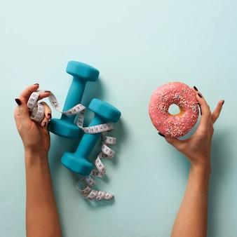 Женская рука держа сладкий пончик, измерительная лента, гантели на синем фоне.