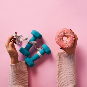 Female hand holding sweet donut, measuring tape, dumbbells over pink background.