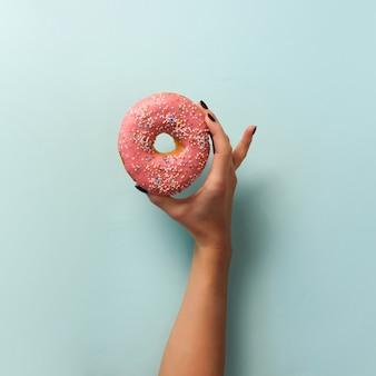Женская рука держа сладкий пончик на синем фоне. Вид сверху, плоская планировка.