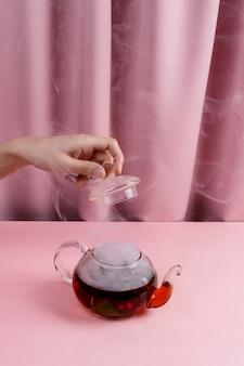 Женская рука держит крышку чайника над чайником с дымящимся фруктово-ягодным чаем