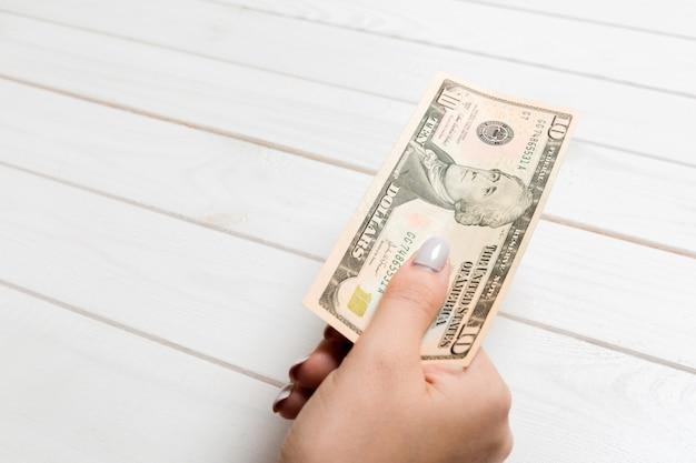 Женская рука держит десятьсот долларов банкноты