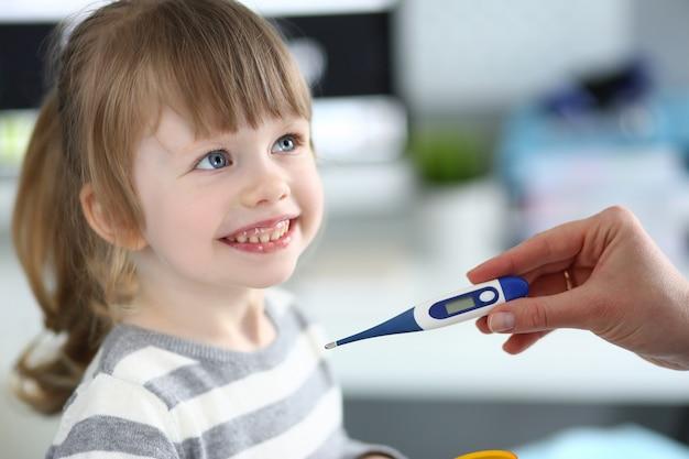 病気の少女を測定する温度計を持っている女性の手