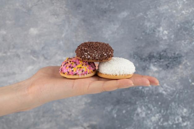Mano femminile che tiene tre biscotti freschi con granelli colorati su una superficie di pietra