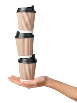 Женская рука, держащая три одноразовых бумажных стаканчика на вынос, изолированные на белом фоне.
