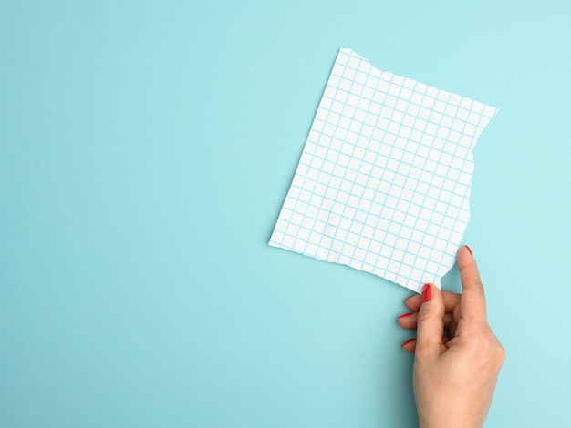 Female hand holding a torn blank sheet of paper in a cage on a blue background