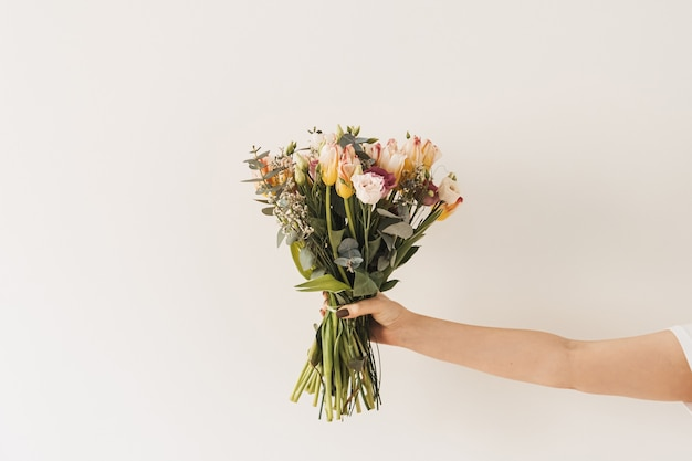 Female hand holding tulip flowers bouquet against white wall