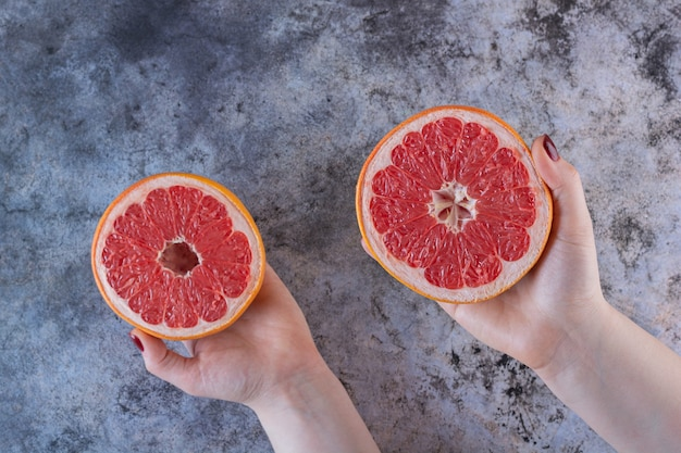 Female hand holding two grapefruit slices on grey.
