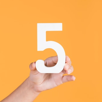 Female hand holding up the number 5 against a yellow background