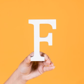 Female hand holding up the uppercase capital letter f