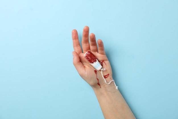 Женская рука держит тампон на синей поверхности