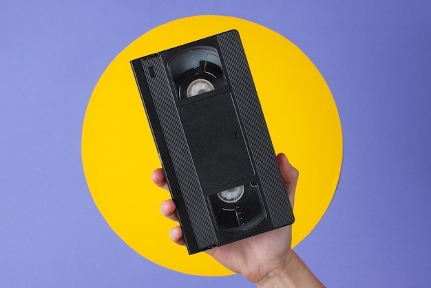 Female hand holding video cassette on purple with yellow circle