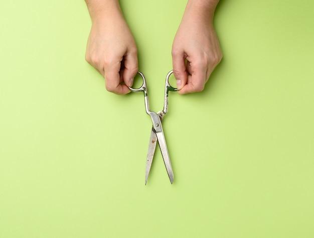 分離されたヴィンテージの金属はさみを持っている女性の手