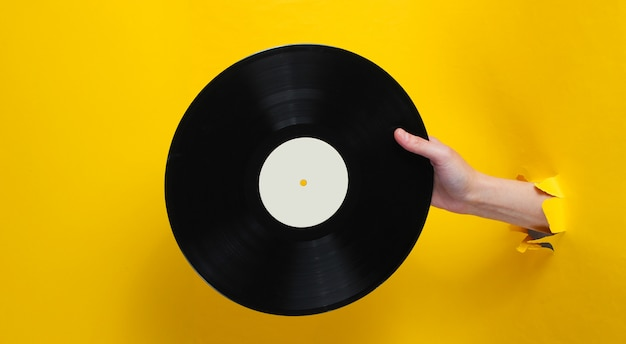 Female hand holding vinyl record through the torn yellow paper hole. minimalistic retro concept