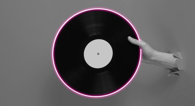 Female hand holding vinyl record with neon circle through the torn paper