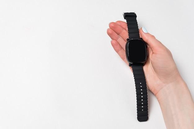 時計を持っている女性の手。白い背景の上の手で腕時計。分離、コピースペース