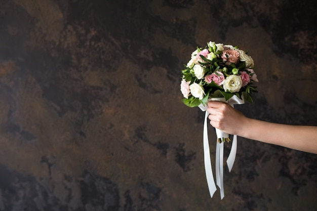 Female hand holding a wedding bouquet on dark