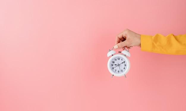Female hand holding white alarm clock on pink background