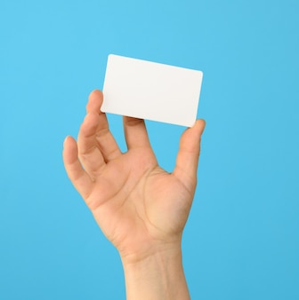 Female hand holding a white black business card, blue background Premium Photo