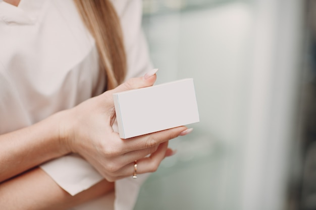 Female hand holding white blank box package