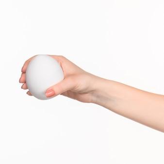 La mano femminile che tiene ovale in polistirolo bianco vuoto contro lo sfondo bianco con l'ombra giusta