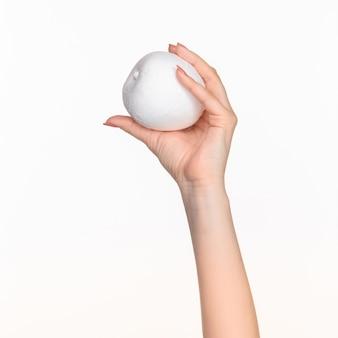 Mano femminile che tiene ovale di polistirolo bianco vuoto contro lo sfondo bianco con ombra a destra